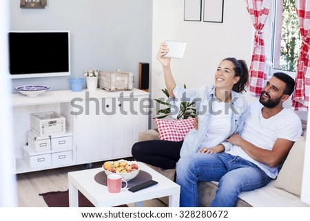 Happy couple on bed sofa in living room,taking selfie on tablet - stock photo