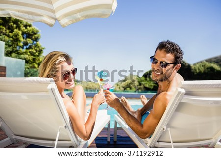 Happy couple on deck chair holding cocktails poolside - stock photo