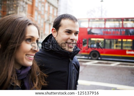 Happy couple on holidays walking around the city and smiling - stock photo