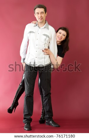 Happy couple  on red burgundy background - stock photo
