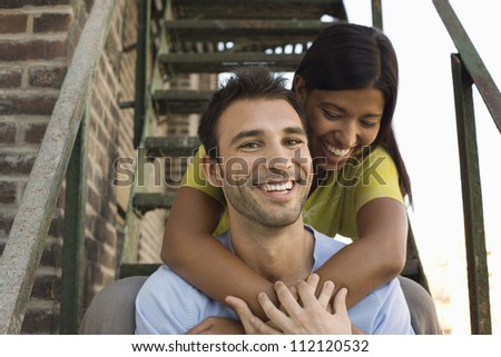 Happy couple on steps spending time together - stock photo