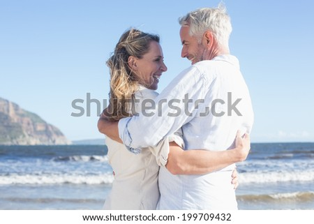 Happy couple on the beach smiling at each other on a sunny day - stock photo