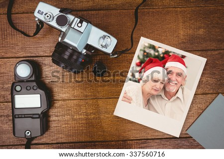 Happy couple on the couch at christmas against view of an old camera with photo flash - stock photo