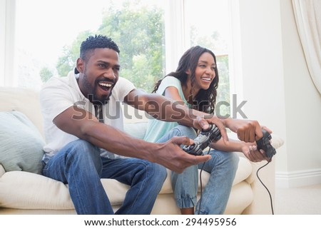 Happy couple on the couch playing video games at home in the living room - stock photo