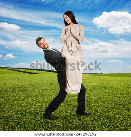 happy couple on the green field. smiley man holding on the hands his beautiful woman and looking at camera - stock photo