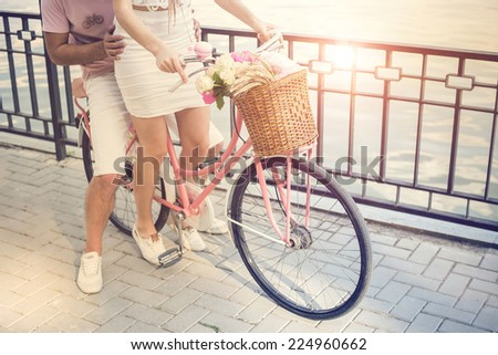 Happy couple on the vintage bicycle with basket and flowers - stock photo