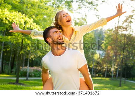 Happy couple on vacation. Lovers are laughing. Happy guy and girl. Lovers enjoy each other in the evening park. - stock photo