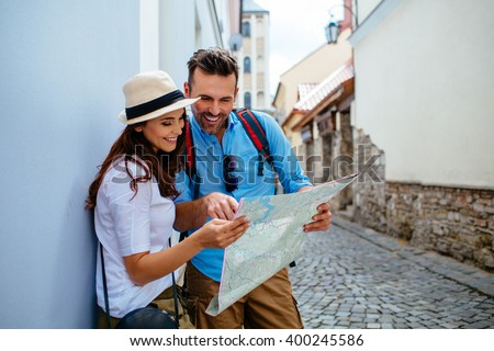 Happy couple on vacation sightseeing city with map - stock photo