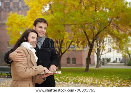 Happy couple on vacation using a city map in autumn - stock photo