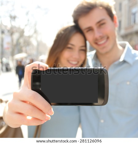 Happy couple or friends making a selfie photo with a smart phone and showing a blank screen to the camera - stock photo