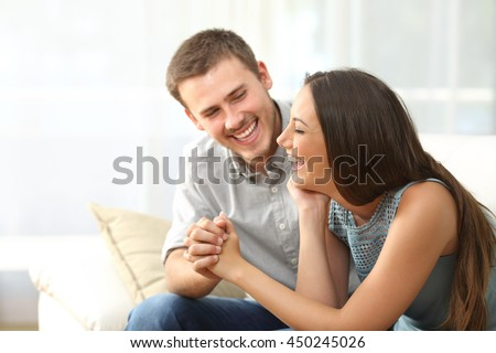 Happy couple or marriage looking each other laughing and holding hands sitting on a sofa at home - stock photo