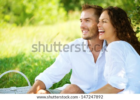 Happy Couple Outdoor. Smiling Couple Relaxing in a Park. Family over Nature Green Background. Smiling Man and Woman Having Picnic in Countryside. Relationships  - stock photo