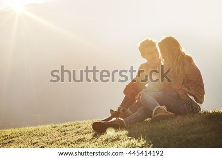 Happy couple outdoors sitting on the grass and spending time together in the sunlight, love and romance concept - stock photo