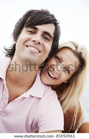 happy couple outdoors, smiling at camera - stock photo