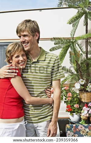 Happy Couple Outside Their Trailer - stock photo