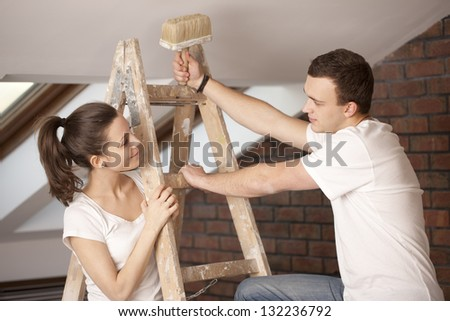 Happy couple painting a wall in their new home in Poland - stock photo