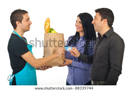 Happy couple paying by credit card their food at grocery to a salesperson man in blue apron isolated on white background - stock photo