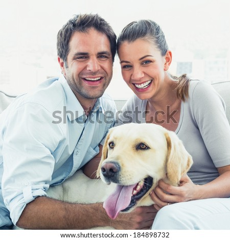 Happy couple petting their yellow labrador on the couch at home in the living room - stock photo