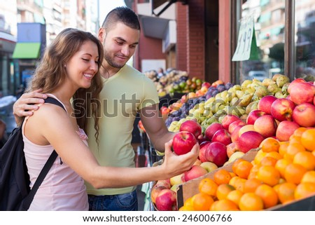 Happy couple picking fruits out on outdoor market   - stock photo