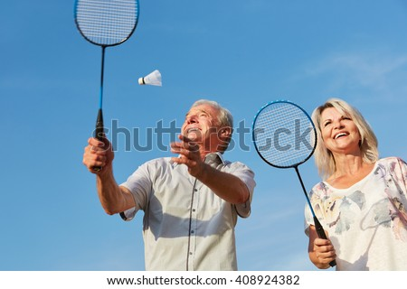 Happy couple playing badminton in summer - stock photo