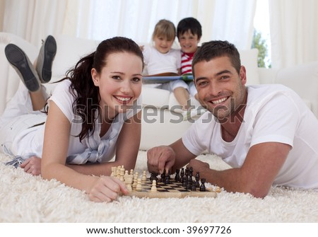 Happy couple playing chess on floor in living-room with their children on sofa - stock photo