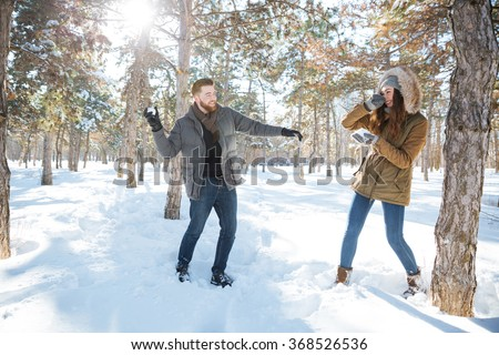 Happy couple playing with snow in winter park. Snowball fight - stock photo