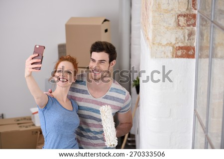 Happy couple posing for a selfie in their new home standing close together with a paint roller alongside an unfinished white wall - stock photo