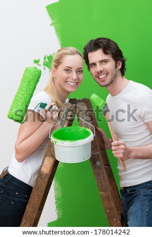 Happy couple redecorating their new house standing on a wooden stepladder painting the wall a bright green and smiling at the camera - stock photo