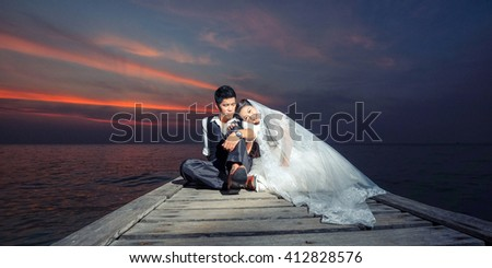 Happy couple relaxing and smile on the wood bridge in sunset - stock photo