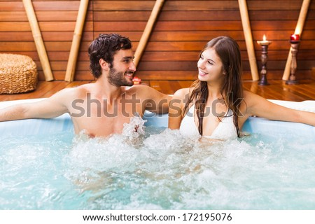 Happy couple relaxing in a hot tub - stock photo