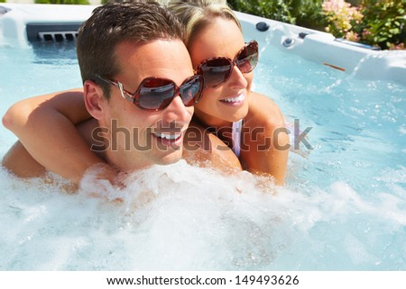Happy couple relaxing in hot tub. Vacation. - stock photo