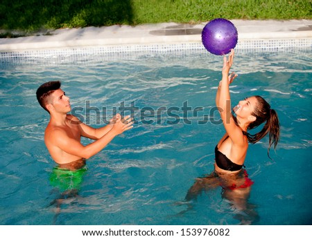 Happy couple relaxing in the pool in the summer playing with a ball - stock photo