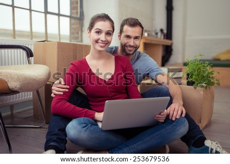 Happy couple relaxing in their new home sitting on the floor using a laptop computer with cardboard boxes visible behind them - stock photo