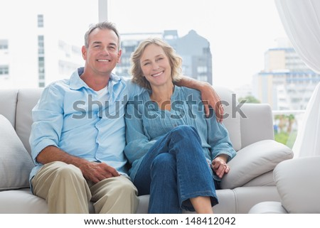 Happy couple relaxing on their couch smiling at camera at home in the sitting room - stock photo