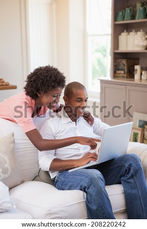 Happy couple relaxing together on the couch using laptop at home in the living room - stock photo