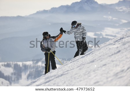 happy couple representing success and winner team concept while handshaking on top of mountain at beautiful sunny winter day - stock photo