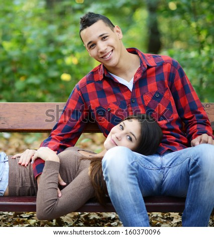 Happy couple resting at park bench - stock photo