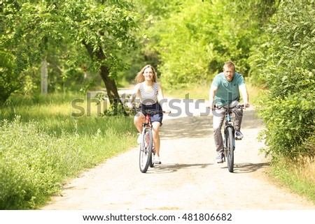 Happy couple riding bicycles in the park