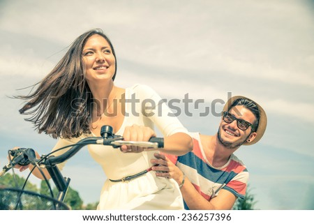 Happy couple riding bikes in the city - Young pretty woman driving bicycle and playful man sitting behind - Portrait of two lovers outdoors - stock photo