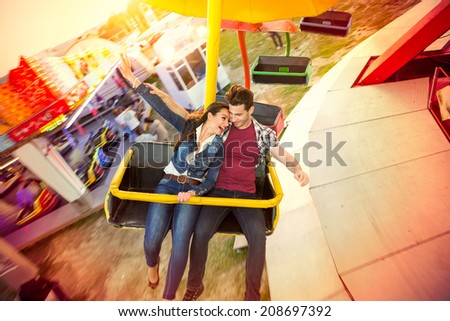 Happy couple riding on ferris wheel at amusement park - stock photo