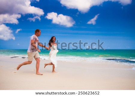 happy couple running at the beach
