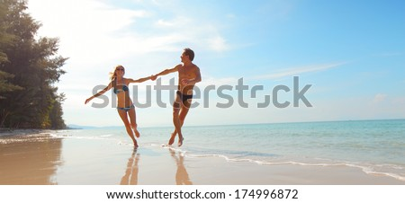 Happy couple running on the beach at sunny day - stock photo