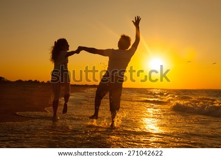 happy couple running on the beach on sunset