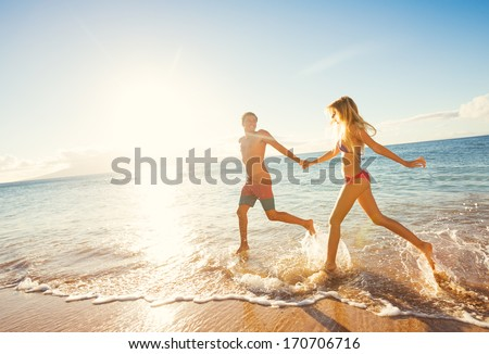 Happy Couple Running on Tropical Beach at Sunset, Vacation  - stock photo