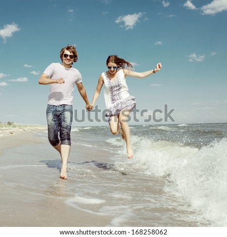 happy couple running on waves on the beach - stock photo