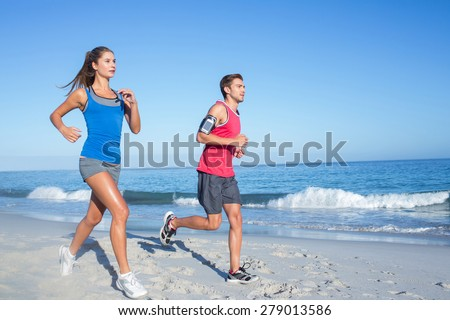 Happy couple running together beside the water at the beach - stock photo