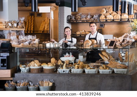 Happy couple selling fresh pastry and loaves in bread section - stock photo