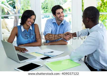 Happy couple shaking hands with real estate agent at home - stock photo