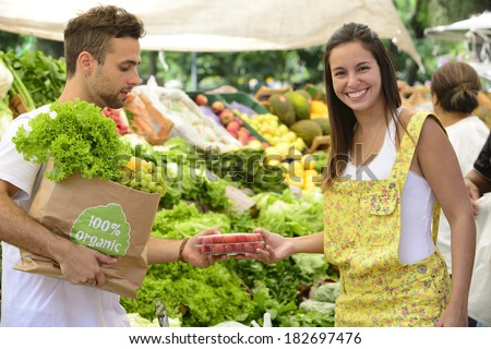 Happy couple shopping fruits and vegetables at a open street market, carrying a shopping paper bag with a 100% organic certified label full of fruit and vegetables. - stock photo