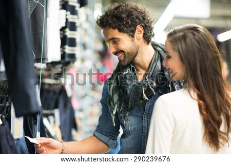 Happy couple shopping in a dress shop - stock photo